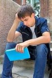 Ledsen student med boken Royaltyfri Bild