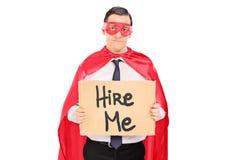 Ledsen superhero med ett tecken som söker efter jobb royaltyfri fotografi