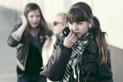 Ledsen tonårig flicka med en mobiltelefon i stadsgata Fotografering för Bildbyråer