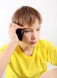 Ledsen tonåring med mobiltelefonen Arkivfoton