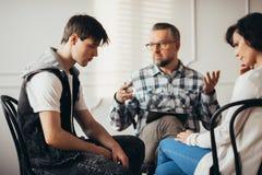 Ledsen tonåring som lyssnar till hans psychatrist under besök i mentalt sjukhus med hans moder arkivfoton
