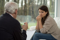 Ledsen tonåring som talar med psykologen Royaltyfri Foto