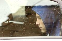 Ledsen tonåringpojke som oroas inom en bil royaltyfria bilder
