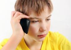 Ledsen tonåring med mobiltelefonen Arkivbild