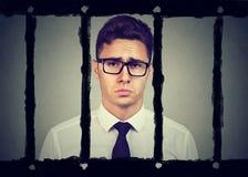 Ledsen ung affärsman i fängelse royaltyfri foto