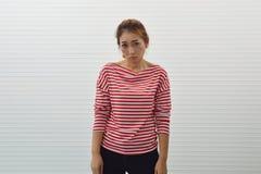 Ledsen ung asiatisk kvinna som bär den röda och vit avriven skjortan och jeans som står över väggbakgrund, frustrerat ansiktsuttr royaltyfri bild