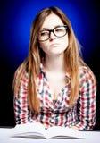 Ledsen ung flicka med nerdexponeringsglas och den öppna skrivboken Arkivfoto