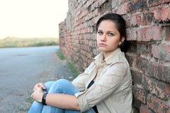 Ledsen ung flicka nära en tegelstenvägg Royaltyfri Foto
