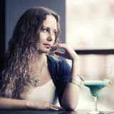 Ledsen ung kvinna med coctailen som ut ser fönstret Royaltyfri Bild