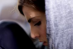 Ledsen ung kvinna med huven som tänker känsligt borttappat sammanträde på soffacloseupen royaltyfri bild