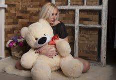 Ledsen ung kvinna med leksakbjörnen Arkivfoto