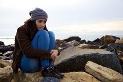 Ledsen ung kvinna som framme sitter av havet Arkivbild