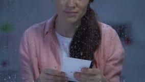 Ledsen ung kvinna som ser fotoet nära det regniga fönstret, saknat barn efter skilsmässa arkivfilmer
