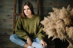 Ledsen ung mörk haired kvinna i ett varmt stuckit mörkt - grön tröja, jeans som poserar i studio med dagsljus fotografering för bildbyråer