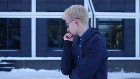 Ledsen ung man i exponeringsglas på grå bakgrund stock video