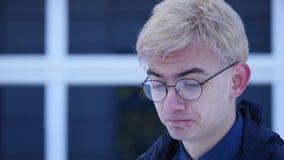 Ledsen ung man i exponeringsglas på grå bakgrund arkivfilmer