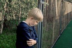 Ledsen uppriven pojke arkivfoton