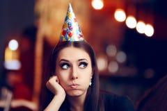 Ledsen uttråkad kvinna på ett parti som har ingen gyckel royaltyfria foton