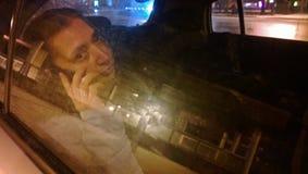 Ledsen vuxen kvinna som talar på telefonen i baksätet av bilen royaltyfri fotografi