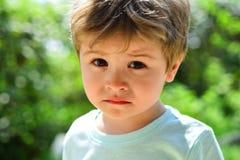 Ledset barn, närbildstående Ett frustrerat barn utan lynne Ledsna sinnesrörelser på en härlig framsida Barn i natur royaltyfri fotografi