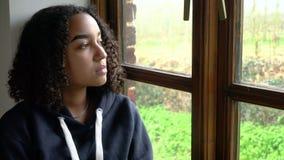 Ledset Biracial sammanträde för ung kvinna för afrikansk amerikanflickatonåring som ser ut ur ett fönster stock video