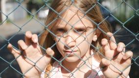 Ledset deprimerat barn i den övergav olyckliga tillfälliga flickaungeföräldralöns som ser kameran royaltyfri foto
