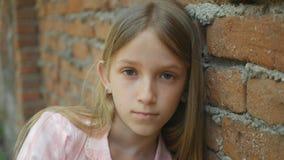 Ledset deprimerat barn som in camera ser, uttråkad flickastående, olycklig ungeframsida royaltyfri foto
