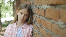 Ledset deprimerat barn som in camera ser, uttråkad flickastående, olycklig ungeframsida fotografering för bildbyråer