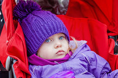 Ledset eller uttråkat liten flickasammanträde i sittvagn Royaltyfri Foto