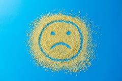 Ledset emojileende på en blå bakgrund Smiley från gula sockerkorn barn för kvinna för bildståendemateriel royaltyfria bilder