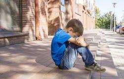 Ledset, ensamt, olyckligt besviket barn som bara sitter på jordningen gata för bakgrundsstadsnatt utomhus- royaltyfri fotografi