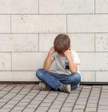 Ledset, ensamt, olyckligt besviket barn som bara sitter på jordningen Pojken som rymmer hans huvud, ser ner utomhus- Royaltyfria Bilder