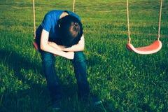 Ledset ensamt pojkesammanträde på gunga royaltyfria foton