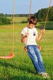Ledset ensamt pojkesammanträde på gunga Fotografering för Bildbyråer