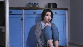 Ledset ensamt ungt asiatiskt flickasammanträde på golvet i kök som rymmer henne knä med armar, familjevåldbegrepp 50 lager videofilmer