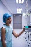 Ledset flickaanseende med iv-droppande i korridor royaltyfri fotografi