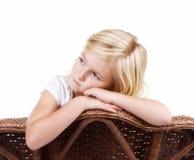 Ledset flickasammanträde i stol royaltyfria foton