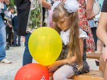 Ledset flickasammanträde med bollar i händer, på September 1 ferie Arkivfoto
