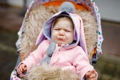Ledset gråta litet härligt behandla som ett barn flickan som sitter i pramen eller sittvagnen på höstdag Olyckligt trött och utma royaltyfria bilder