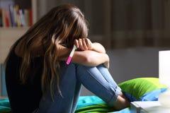 Ledset gravid tonårigt efter graviditetstest arkivfoton