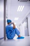 Ledset kirurgsammanträde på golv i korridor royaltyfri fotografi