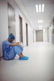 Ledset kirurgsammanträde på golv i korridor arkivbild