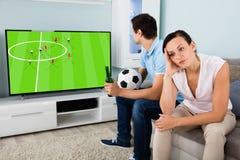 Ledset kvinnasammanträde bredvid en upptagen hållande ögonen på fotboll för man royaltyfri fotografi