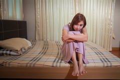 Ledset kvinnasammanträde på sängen Arkivfoto