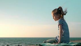 Ledset liten flickasammanträde på bryggan på stranden under stormcloseupen stock video