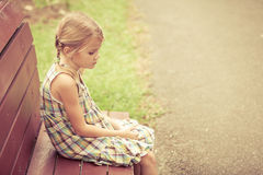 Ledset liten flickasammanträde på bänk i parkera Arkivbild