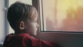 Ledset och ensamt se för barn till och med fönster Barnet är deprimerat stock video