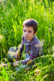 Ledset pojkesammanträde i gräs Arkivfoton