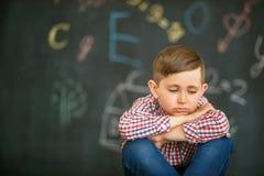 Ledset pojkesammanträde med stängda ögon mot bakgrunden av skolförvaltningen royaltyfri foto