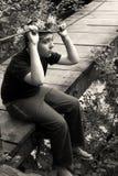 Ledset pojkesammanträde på träbron royaltyfri foto